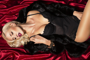 sexy blond woman in fur coat lying on the red material