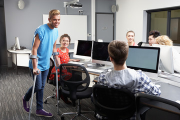 Male Pupil Walking On Crutches In Computer Class