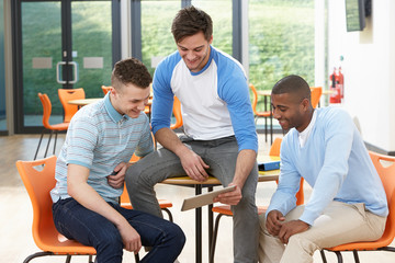 Three Male Students Looking At Digital Tablet In Classroom