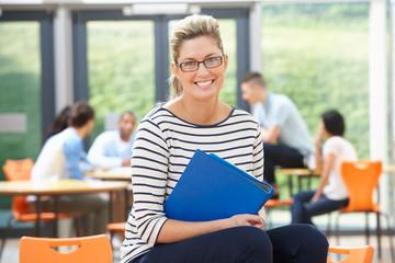 Female Tutor Sitting In Classroom With Folder