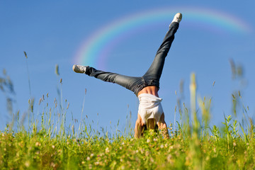 Young woman doing cartwheel with rainbow behind