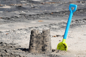 Sand castle and a plastic shovel at a beach
