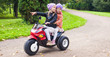 Happy little cute girls ride a motorbike outside