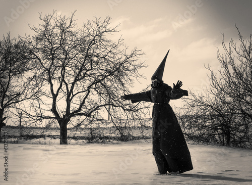 Strange person in black cloak in winter day