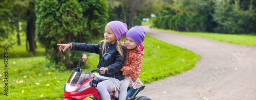 Adorable little girls riding on kid's bike in the green park