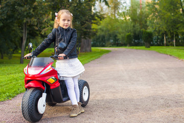 Beautiful little girl having fun on her toy motorcycle outdoors