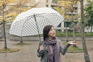 Happy smiling Asian woman holding an umbrella