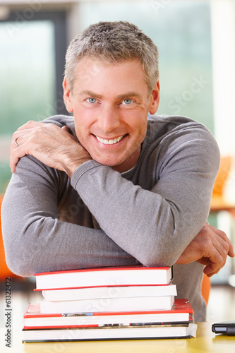 Male Mature Student Studying In Classroom With Books
