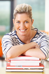 Mature Female Student Studying In Classroom With Books