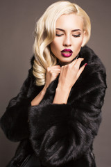 sexy blond woman in black fur coat