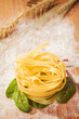 Fresh pasta and lettuce on a wooden table