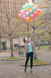Young woman playing and holding balloons