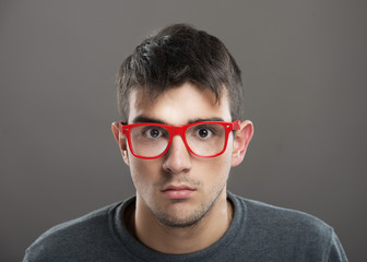Teenage boy in red-framed eyeglasses looking at camera