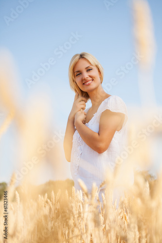 Woman in wheat field enjoying beautiful summer day