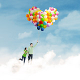 Young couple holding colorful balloons