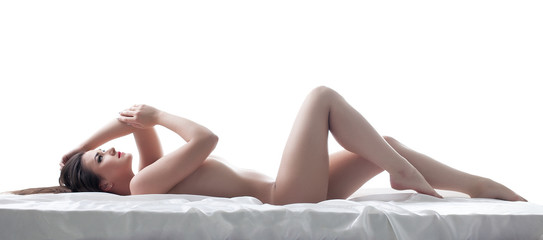 Sexy young brunette posing nude, lying in studio