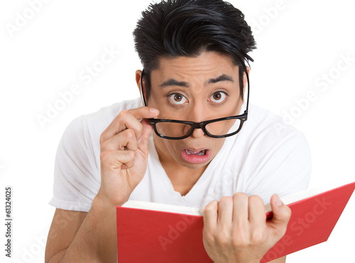 Shocked man in glasses reading a book