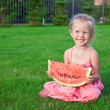 Little girl with big piece of watermelon in hands on green grass