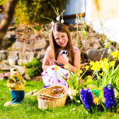 Girl on Easter egg hunt with living Easter Bunny