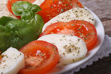 Italian Caprese salad of mozzarella, basil and tomato. closeup