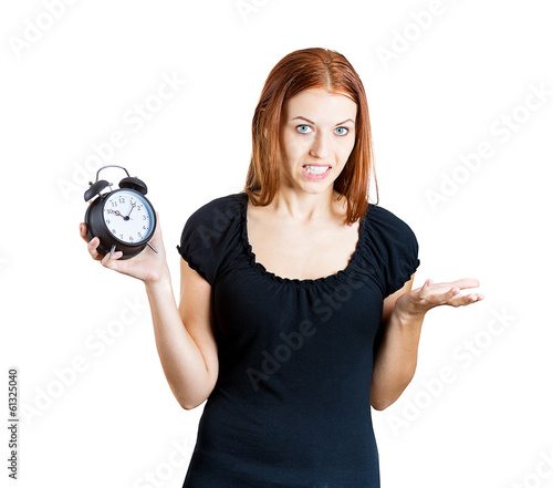 Woman holding alarm clock, running late for meeting