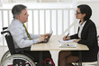Businessman in wheelchair  having meeting with Businesswoman