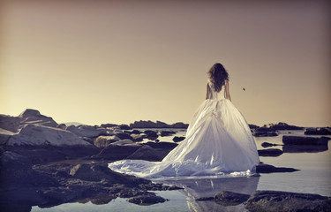 Young bride standing on a cliff at the sea