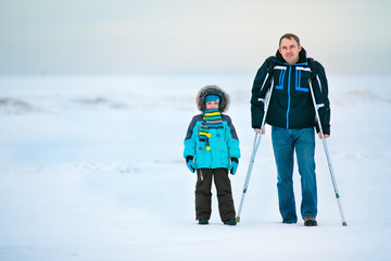 Man with crutches and his son walking outdoors