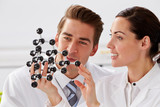 Two Technicians Looking At Molecular Model In Laboratory