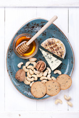 Various types of cheese with honey and nuts. Cheese plate.