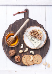 Various types of cheese with honey and nuts. Cheeseboard.