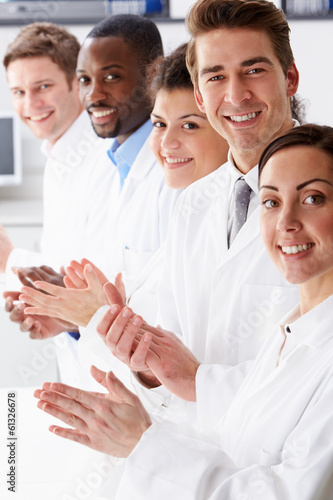 Portrait Of Technician And Colleagues In Laboratory Clapping