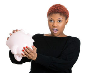 Woman with financial problems holding empty piggy bank