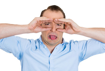 Funny displeased man looking through imaginary binoculars