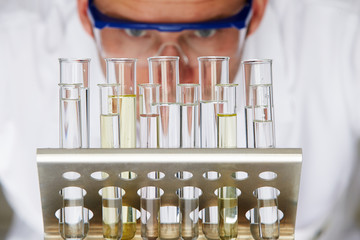 Scientist Studying Test Tubes In Rack