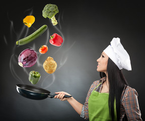 Skillful cook lady throwing veggies