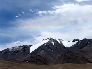 パミール高原、雪山にかかる虹