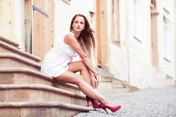 Beautiful young woman in white dress posing outdoor.