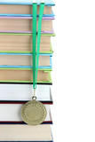 Medal for achievement in education with books isolated on white