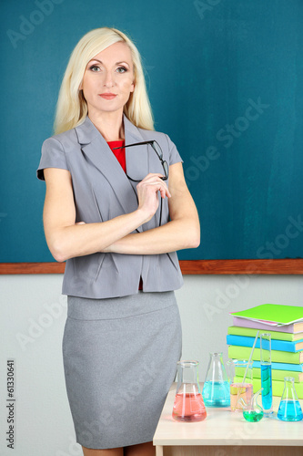 Chemistry teacher standing near table with tubes