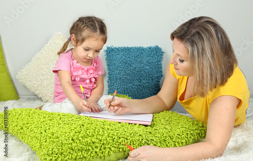 Little girl with mom read book in bed