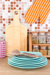 Plates in kitchen on table on mosaic tiles background