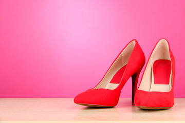 Beautiful red female shoes, on pink background