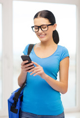 smiling female student with smartphone and bag