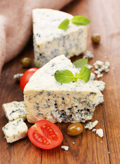 Tasty blue cheese with tomato, olives and basil, on wooden