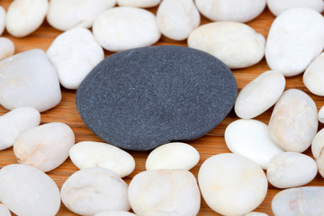 A black stone and many small white stones