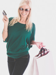 Young smiling woman with credit card and shopping bags
