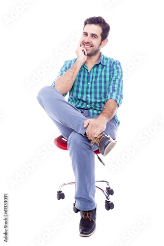 Portrait of a thoughtful man sitting on the chair, isolated on w