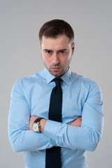 Angry business man on grey background