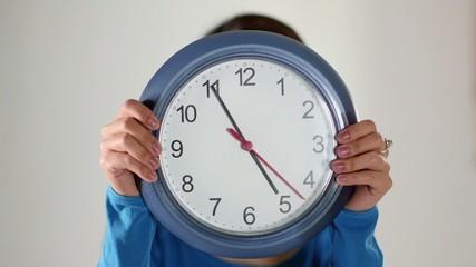 asian girl hiding behind big clock
